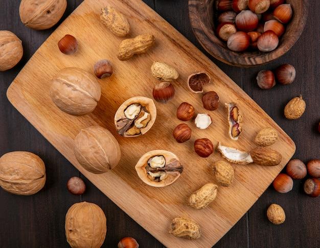 Vista de cima nozes com avelãs e amendoim em uma placa sobre uma mesa de madeira