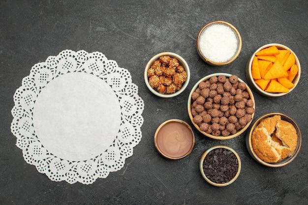 Vista de cima nozes doces com flocos de cacau e cips na superfície escura, lanche com leite, refeição com leite, noz do café da manhã