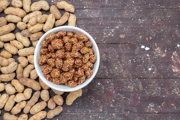 Vista de cima nozes doces junto com amendoim na mesa de madeira, porca, amendoim doce lanche
