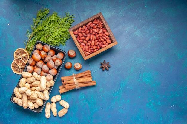 Vista de cima, nozes frescas, canela, avelãs e amendoins dentro do prato, no fundo azul, cor de noz, lanche, cips, foto, planta, árvore