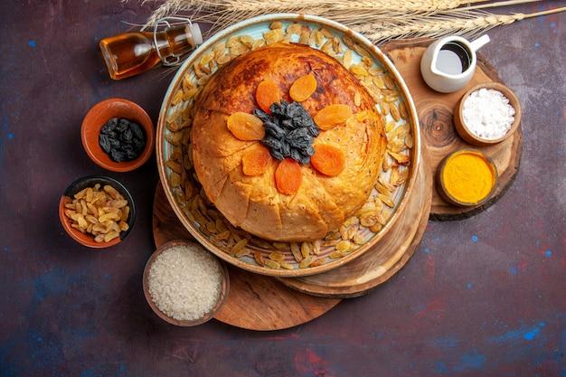 Vista de cima, o delicioso shakh plov cozido refeição de arroz com passas na superfície escura refeição jantar massa de comida cozinhar arroz