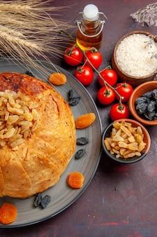 Vista de cima, o delicioso shakh plov cozinhou farinha de arroz com passas e tomates na mesa escura de massa de farinha cozinhando arroz de jantar
