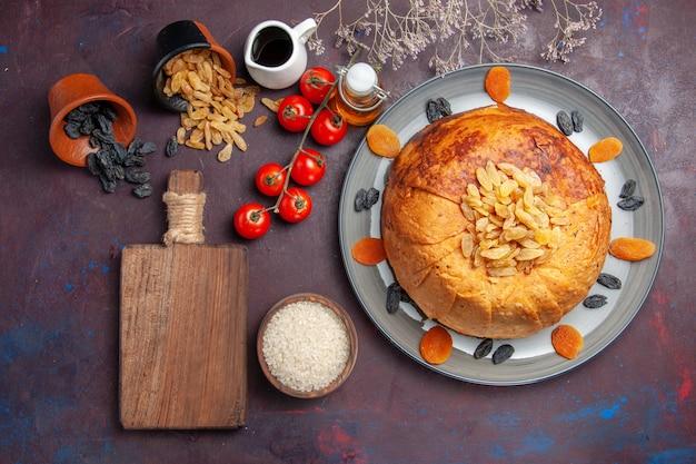 Vista de cima, o saboroso shakh plov cozinhou a refeição de arroz dentro da massa com tomates na superfície escura.