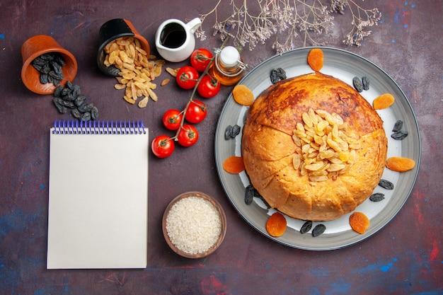 Vista de cima, o saboroso shakh plov cozinhou farinha de arroz dentro da massa com tomates em um fundo escuro comida de arroz cozinhando