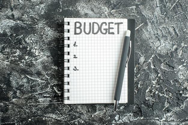 Vista de cima orçamento escrito nota no bloco de notas com caneta na cor de fundo cinza caderno escolar estudante universitário lição escura negócios dinheiro