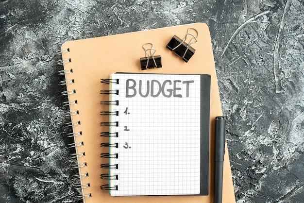 Vista de cima orçamento escrito nota no bloco de notas com caneta na superfície escura cinza cor do aluno dinheiro da escola caderno de negócios da faculdade