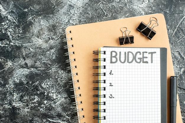Vista de cima orçamento escrito nota no bloco de notas com caneta na superfície escura cor do aluno dinheiro da escola cinza caderno da faculdade