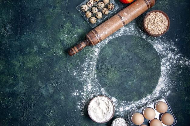 Vista de cima os diferentes ingredientes da massa, farinha branca, cereais e ovos na superfície azul-escura