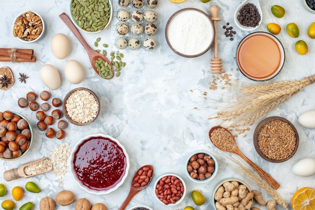 Vista de cima os diferentes ingredientes da torta, geléia, ovos, sementes, nozes e farinha na massa branca, bolo, biscoito doce, açúcar, foto, noz