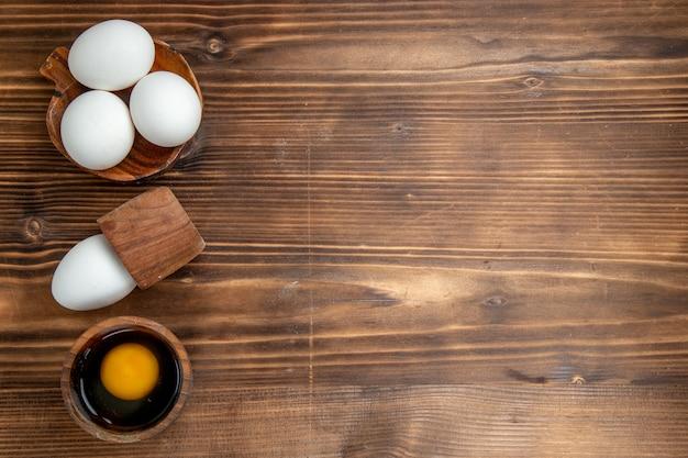 Vista de cima ovos crus produtos inteiros em um fundo marrom ovo comida refeição café da manhã almoço pão saúde