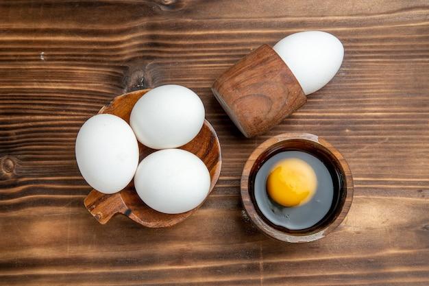 Vista de cima ovos crus produtos inteiros na superfície marrom ovo comida refeição café da manhã almoço pão saúde