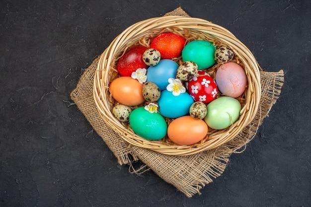 Vista de cima ovos de páscoa coloridos dentro da cesta em superfície escura