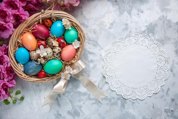 Vista de cima ovos de páscoa coloridos dentro da cesta na superfície branca conceito ornamentado do feriado da flor colorida da primavera