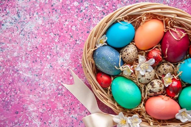 Vista de cima ovos de páscoa coloridos dentro da cesta na superfície rosa primavera flor colorida ornamentado conceito feriado