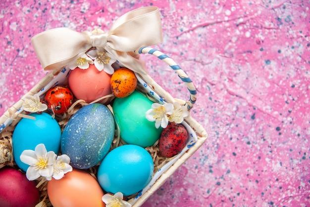 Vista de cima ovos de páscoa coloridos dentro de uma caixa fofa na superfície rosa conceito de cor da primavera ornamentado colorido feriado de páscoa