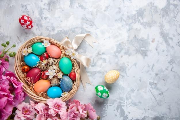 Vista de cima ovos de páscoa coloridos dentro de uma cesta na superfície branca primavera colorida flor de páscoa feriado conceito ornamentado
