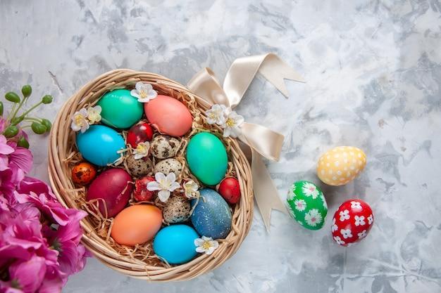 Vista de cima ovos de páscoa coloridos dentro de uma cesta na superfície branca primavera colorida flor de páscoa feriado ornamentado