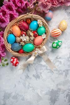Vista de cima ovos de páscoa coloridos dentro de uma cesta na superfície branca primavera flor colorida conceito ornamentado feriado de páscoa
