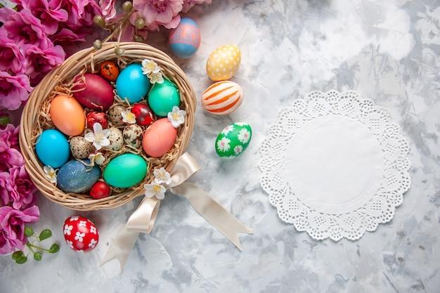Vista de cima ovos de páscoa coloridos dentro de uma cesta na superfície branca primavera flor colorida ornamentado feriado de páscoa