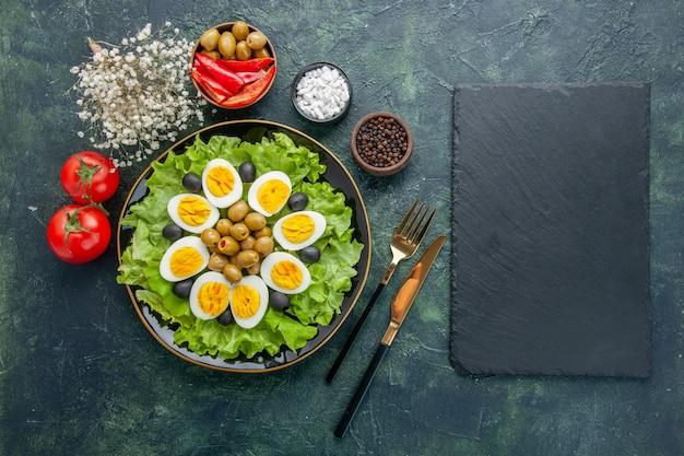 Vista de cima ovos fatiados cozidos com salada verde e azeitonas em fundo azul escuro