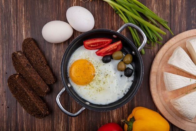 Vista de cima ovos fritos em uma frigideira com tomates, azeitonas e cebolinha, pão preto e queijo feta em um fundo de madeira