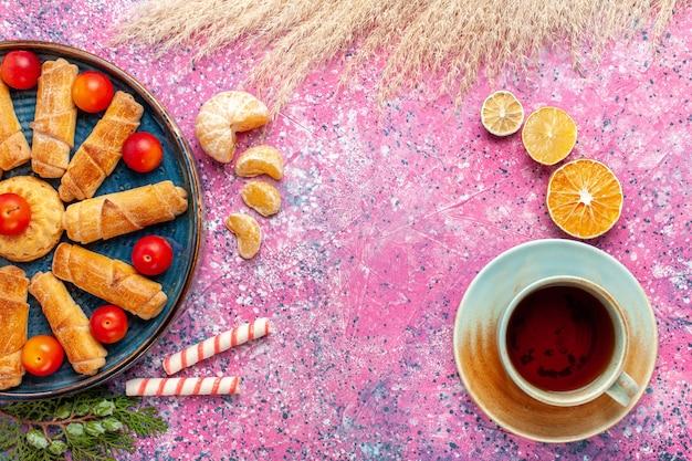 Vista de cima, pães deliciosos e doces dentro da bandeja com ameixas azedas e chá na mesa rosa claro