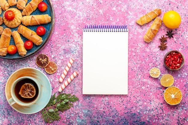 Vista de cima, pães deliciosos e doces dentro da bandeja com ameixas e xícara de chá na mesa rosa