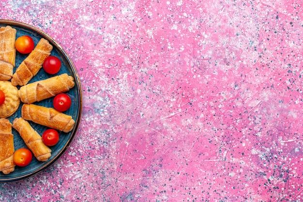Vista de cima, pães deliciosos e doces, tortas assadas dentro da bandeja com ameixas na mesa rosa claro