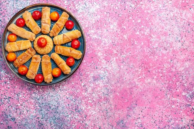Vista de cima, pães deliciosos e doces, tortas assadas dentro da bandeja com ameixas na mesa rosa