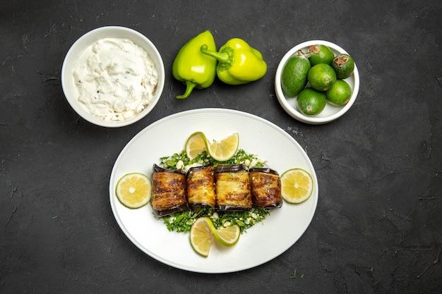 Vista de cima pãezinhos de berinjela salgados prato cozido com rodelas de limão e feijoa na superfície escura do jantar com óleo para cozinhar prato de refeição
