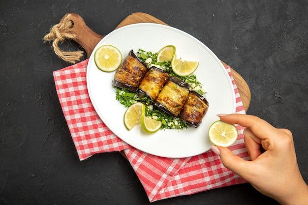Vista de cima pãezinhos de berinjela salgados prato cozido com rodelas de limão na mesa escura jantar óleo cozinhar refeição prato cítrico