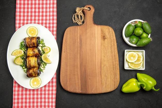 Vista de cima pãezinhos de berinjela salgados prato cozido com rodelas de limão na superfície escura jantar prato de óleo cítrico