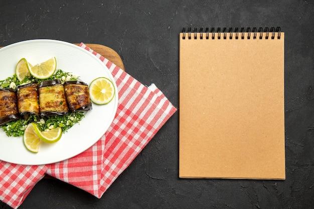 Vista de cima pãezinhos de berinjela salgados prato cozido com rodelas de limão na superfície escura óleo de jantar cozinhar prato prato cítrico