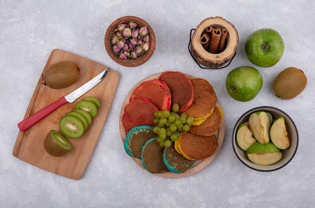 Vista de cima panquecas coloridas com uvas verdes em um suporte com maçãs verdes e kiwi com uma faca em uma placa com canela em um fundo branco