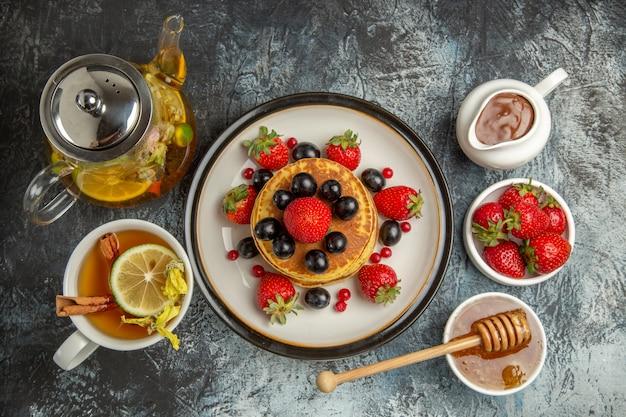 Vista de cima panquecas deliciosas com frutas e chá no café da manhã com frutas doces no chão claro