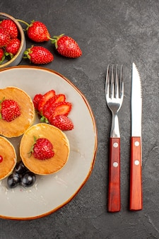 Vista de cima panquecas deliciosas com frutas em bolo de torta cinza escuro