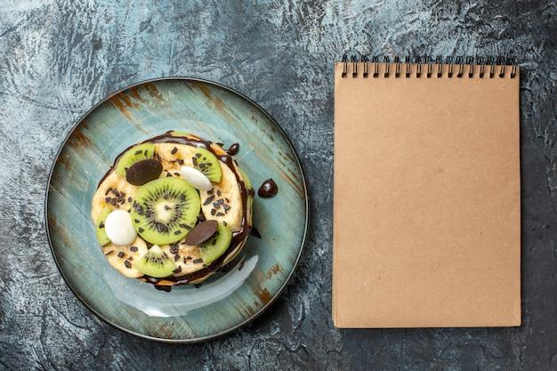 Vista de cima panquecas deliciosas com frutas fatiadas e chocolate em uma superfície de cor escura café da manhã açúcar fruta doce bolo sobremesa