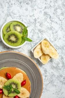 Vista de cima panquecas deliciosas com frutas fatiadas e xícara de chá em uma superfície branca fruta doce sobremesa café da manhã cor bolo açúcar