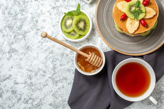 Vista de cima panquecas deliciosas com frutas fatiadas e xícara de chá na superfície branca frutas doce sobremesa açúcar café da manhã cor bolo