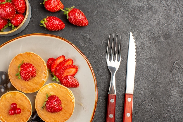 Vista de cima panquecas deliciosas com frutas na superfície cinza-escuro bolo de frutas