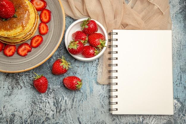 Vista de cima panquecas deliciosas com morangos frescos em uma mesa leve com frutas doces