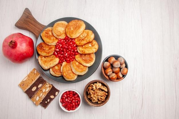 Vista de cima panquecas e romã de romã ao lado das tigelas de geleia e placa de bolo de nozes de panquecas e sementes de romã na tábua de madeira sobre a mesa
