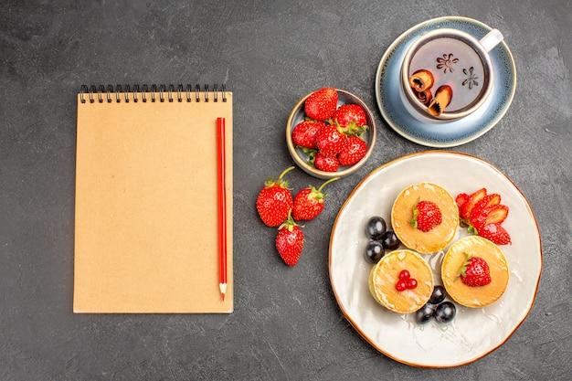 Vista de cima panquecas gostosas com frutas e uma xícara de chá em bolo de torta de fruta com piso cinza