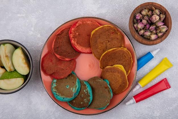 Vista de cima panquecas multicoloridas em um prato laranja com fatias de maçã verde em uma tigela com tintas multicoloridas em tubos em um fundo branco