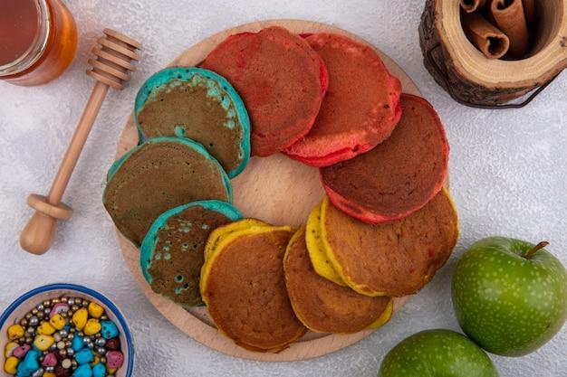Vista de cima panquecas multicoloridas em um suporte com maçãs verdes, chocolates coloridos de canela e mel em um fundo branco