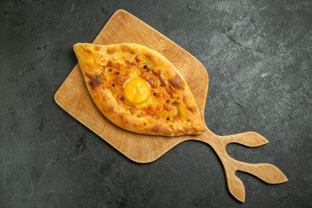 Vista de cima, pão com ovo cozido, delicioso bolo de massa recém-saído do forno no espaço escuro
