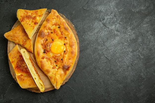Vista de cima, pão com ovo cozido delicioso recém-saído do forno no espaço cinza escuro