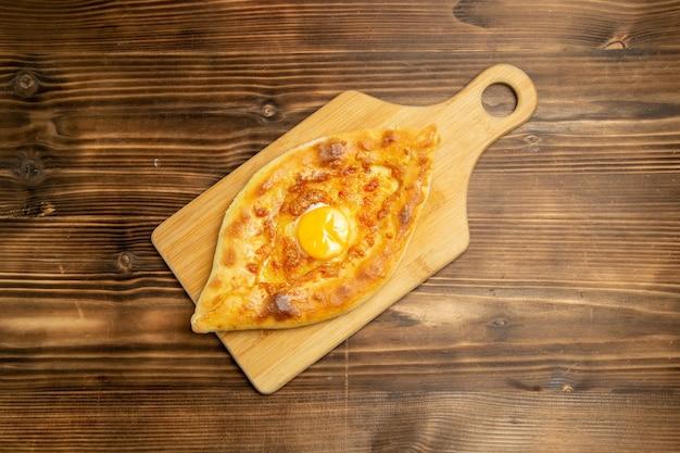 Vista de cima pão com ovo delicioso assado na mesa de madeira marrom pão coque ovo