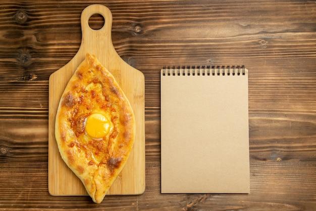 Vista de cima pão com ovo delicioso assado na mesa de madeira marrom pão coque ovos do café da manhã