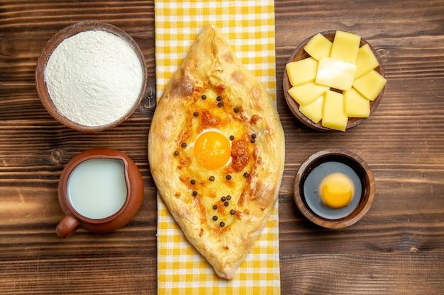 Vista de cima, pão com ovo saboroso recém saído do forno com leite e queijo na mesa de madeira refeição pão pão com ovo